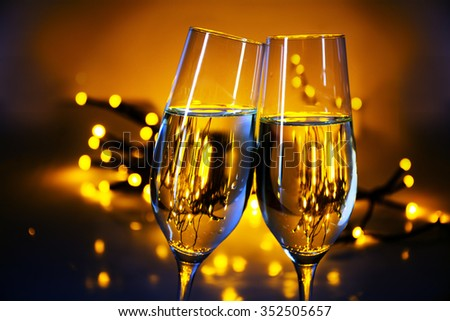 Two champagne flutes clink glasses at Christmas or New Year's  party, warm golden background with blurred lights and copy space - stock photo