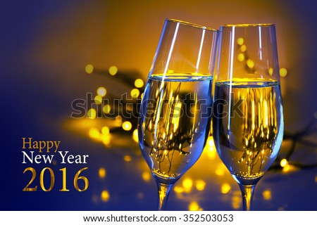 Two champagne flutes clink glasses at the party, blue yellow background with blurred golden lights and text Happy New Year 2016 - stock photo