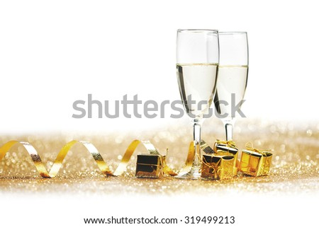 Two champagne glass on golden christmas glitter bokeh background - stock photo