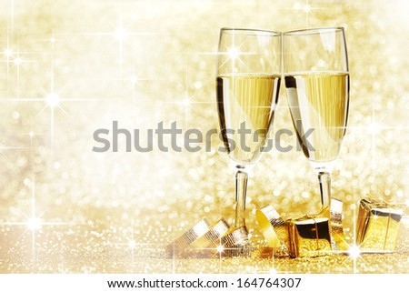 Two champagne glasses, gifts and decoration on golden background - stock photo
