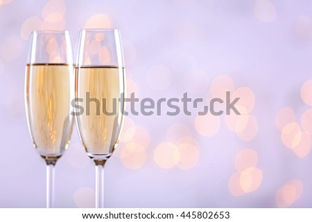 Two champagne glasses on light background - stock photo