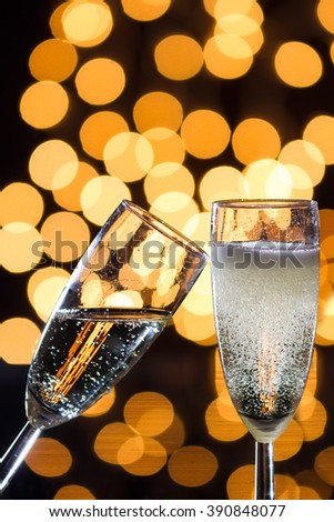 Two champagne glasses with bubbles and bokeh lights in the background - stock photo