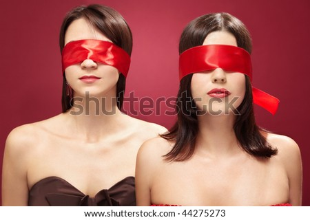 Two charming girls blindfold on a red background - stock photo