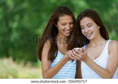 Two charming girls reads message to mobile phone, against green of summer park. - stock photo