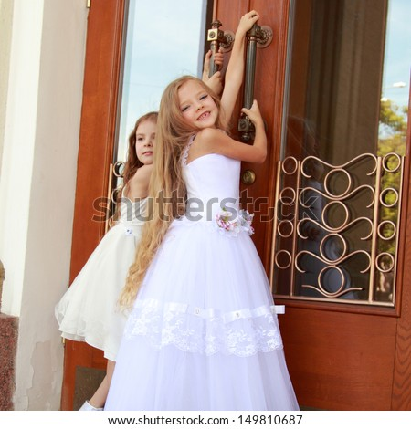 Two charming little girls in long white dresses stand near the mirrored doors of the building outdoors - stock photo