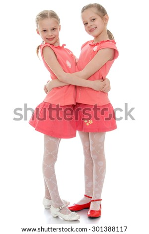 Two charming little girls sisters hug each other. The girls dressed in red T-shirts with short sleeves and short red skirt. Girls twins are very similar to each other-Isolated on white background - stock photo