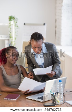 Two cheerful african american business women working at the office on a computer - stock photo