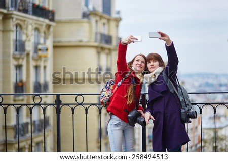 Two cheerful beautiful girls in Paris doing selfie on Montmartre - stock photo