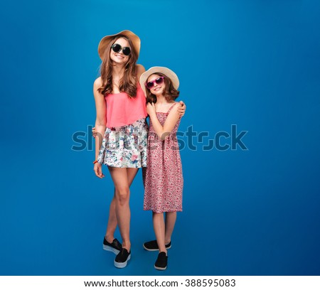 Two cheerful beautiful sisters standing together over blue background - stock photo
