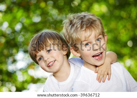 Two cheerful boys embrace in a summer garden - stock photo