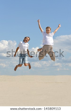 two cheerful boys jumping against the sky - stock photo