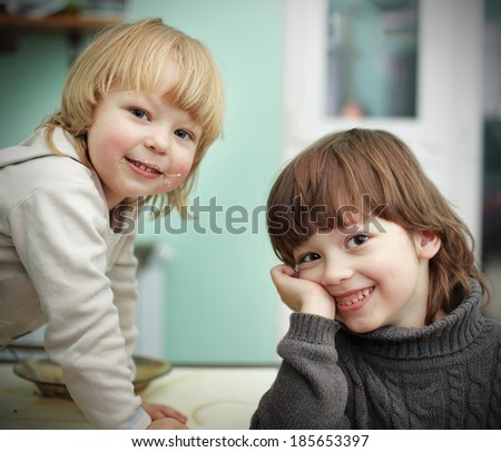 two cheerful brother on the kitchen table - stock photo