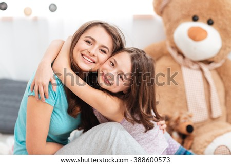 Two cheerful charming sisters smiling and embracing at home - stock photo
