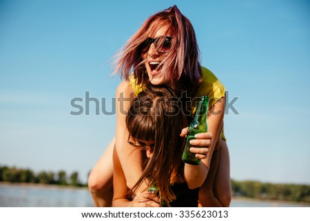 Two Cheerful Females Having Fun At The Beach - stock photo