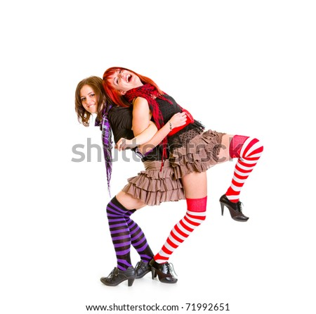 Two cheerful girlfriends standing back to back and  funny posing together isolated on white - stock photo