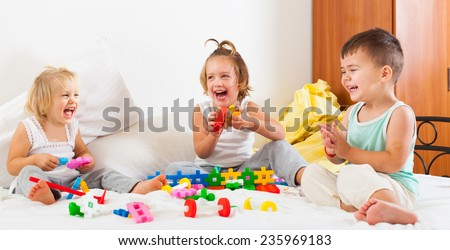 Two cheerful girls and a boy playing on  big bed.  - stock photo