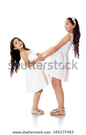 Two cheerful girls are sisters of different ages are dressed in white dresses , holding hands - Isolated on white background.The concept of a Happy childhood and child development - stock photo