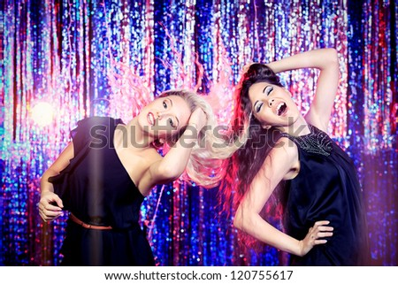 Two cheerful girls dancing at a party. - stock photo
