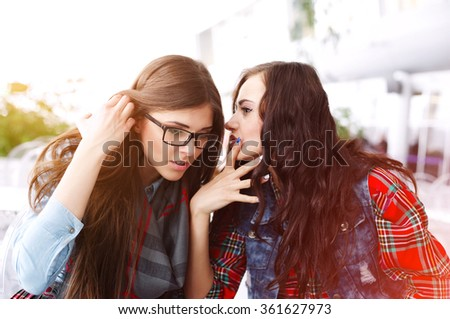 Two cheerful girls gossiping in the cafe. Girl with the stylish sunglasses playing with hair, attentively listening. Fascinating conversation.  - stock photo