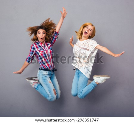 Two cheerful girls jumping over gray background - stock photo