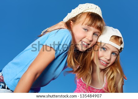 Two cheerful girls outdoor over blue sky. - stock photo