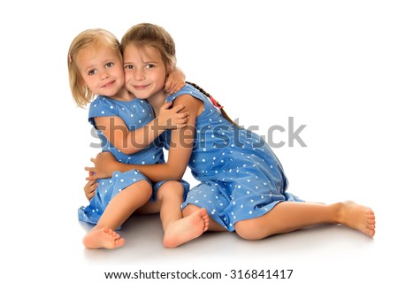 Two cheerful girls sisters in blue summer dresses polka dot frolic on the floor-Isolated on white background - stock photo