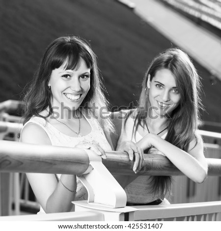 Two cheerful girls stand on the stairs  - stock photo