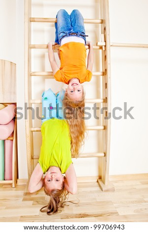 Two cheerful girls upside down - stock photo