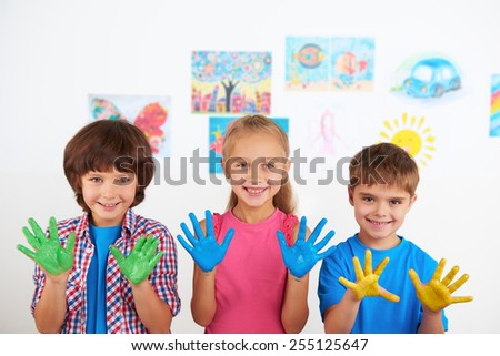 Two cheerful little boys and smiling girl showing at camera painted hands. Preschool center for children - stock photo