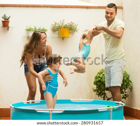 Two cheerful little girls and smiling parents having fun in pool at terrace. Focus on girl