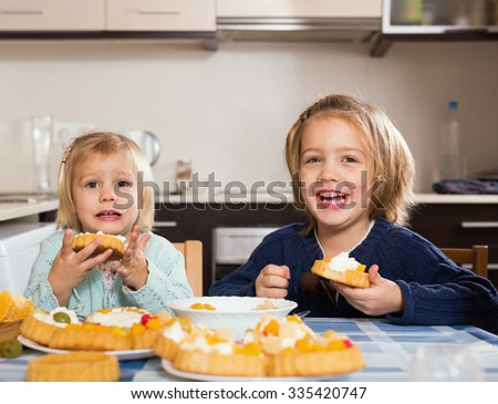 Two cheerful little girls with cream desserts at home kitchen