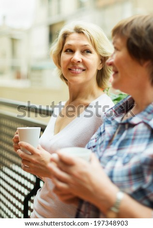 Two cheerful mature women drinking tea on balcony and smiling - stock photo