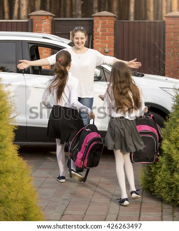 Two cheerful schoolgirls running to mother meeting them after school - stock photo