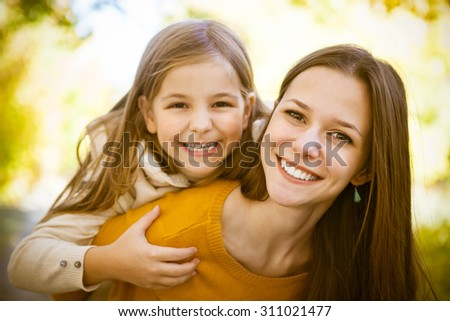 Two cheerful sisters playing in the park in warm autumn day - stock photo