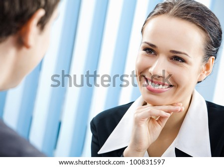Two cheerful smiling young businesspeople, or business woman and client, working at office - stock photo