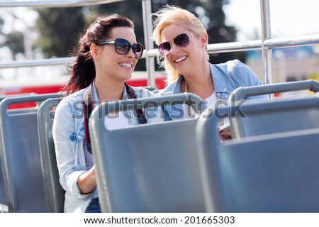 two cheerful tourists enjoying open top bus tour in the city - stock photo