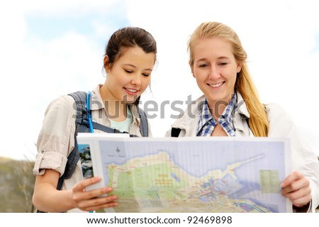 two cheerful women hiking outdoors and consulting their map for the direction in which to travel - stock photo