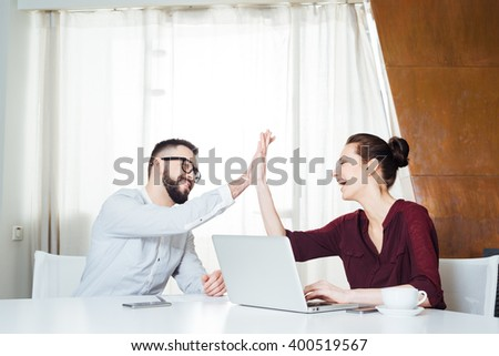 Two cheerful young businesspeople celebrating success and giving high five on the meeting - stock photo