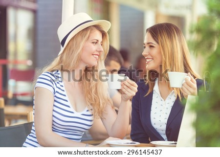 Two cheerful young girlfriends sitting in a cafe drinking coffee and relaxing after shopping - stock photo