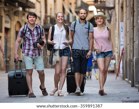 Two cheerful young traveler couples with travel bags walking through the city. Selective focus - stock photo