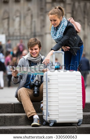 Two cheerful young travelers with city map and baggage looking for hotel - stock photo