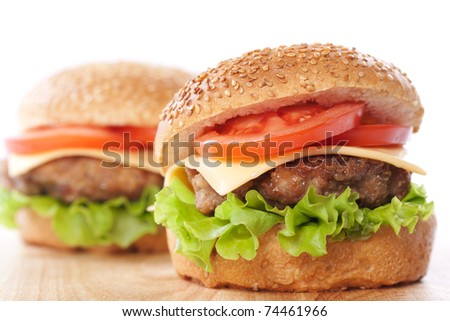 Two cheeseburgers with tomatoes and lettuce on a wooden table - stock photo