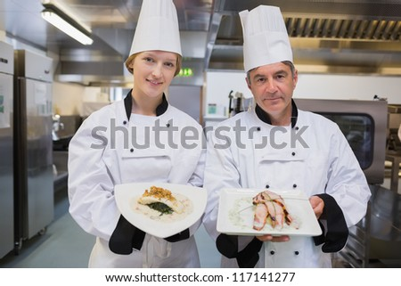Two Chef's presenting their dishes in restaurant kitchen - stock photo