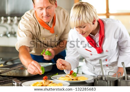 Two chefs in teamwork - man and woman - in a restaurant or hotel kitchen cooking delicious food, both are decorating the dishes - stock photo