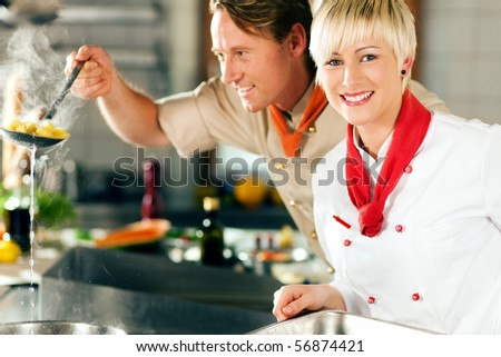 Two chefs in teamwork - man and woman - in a restaurant or hotel kitchen cooking delicious food, he is taking out the pasta - stock photo