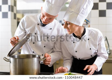 Two chefs - man and woman - in hotel or restaurant kitchen working and cooking in team - stock photo