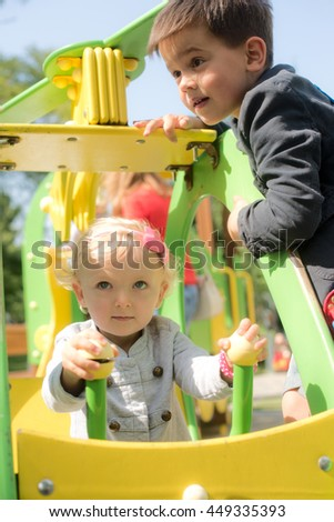 Two children, a boy and a girl playing happily together on Playground - stock photo