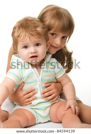 Two children (a girl and a boy) are having fun while sitting on floor, isolated over white - stock photo