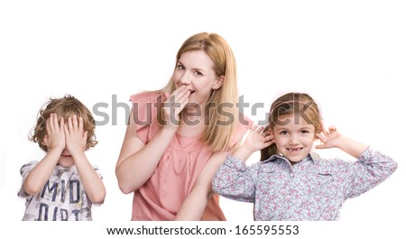 Two children and their mother demonstrate the wisdom of the three wise monkeys; see no evil, say no evil and hear no evil. - stock photo