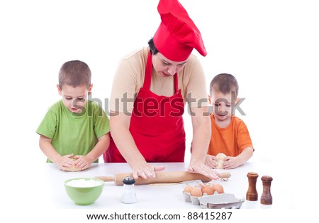 Two children and their mother with a preparation for cookies together in the kitchen - stock photo